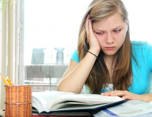 Teenage girl studying with textbooks.